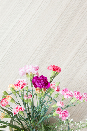 glass cutter: Colorful flowers in glass bowl  on wood background.