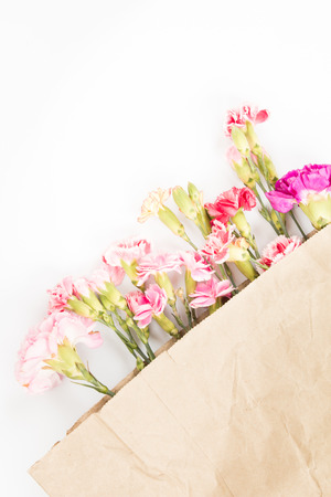 Colorful carnations flowers in paper bag on white background.
