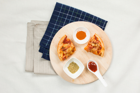 Top view of Hawaiian Pizza with topping on wooden on tablecloth.