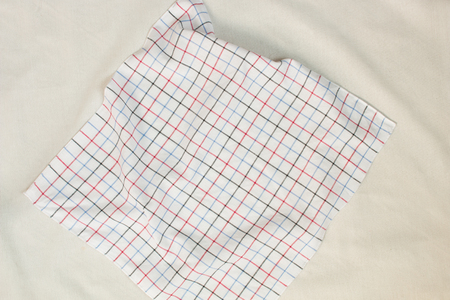 Top view of crumpled white plaid on white background.