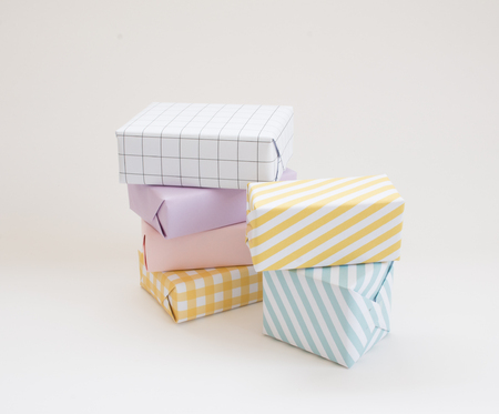 Pastel gift boxes stacked on white background. Stock Photo