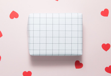 Top view of gift box and red hearts on pink background. Stock Photo