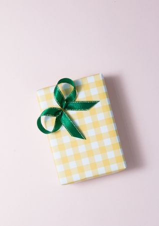 Top view of pastel gift with green bow box on pink background. Stock Photo