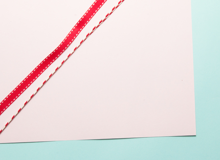 Variety of red ribbons on soft pink and blue paper background.