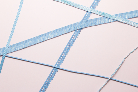 Blue ribbon on soft pink paper background.