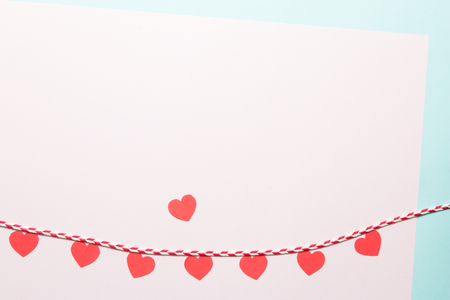 Red rope and heart shapes  on pink paper background