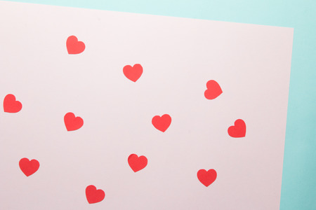 Red heart shapes pattern on pink and blue paper background