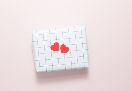 Two red heart shapes on checked and pink paper background.