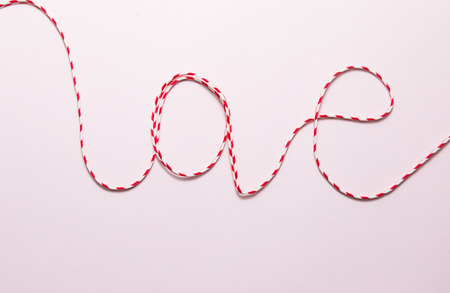 Red rope on soft pink paper background. Stock Photo