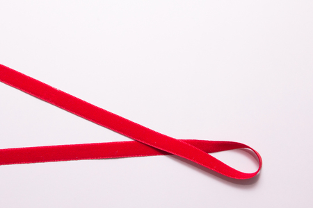 Top view of red ribbon on pink background.