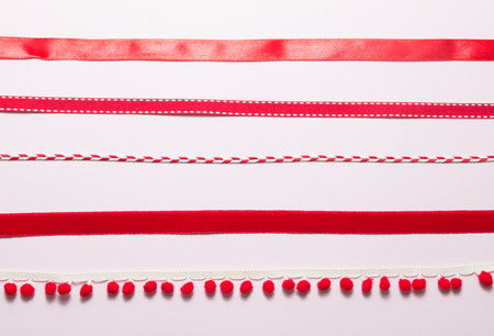 Top view of variety red ribbons on pink background. Stock Photo