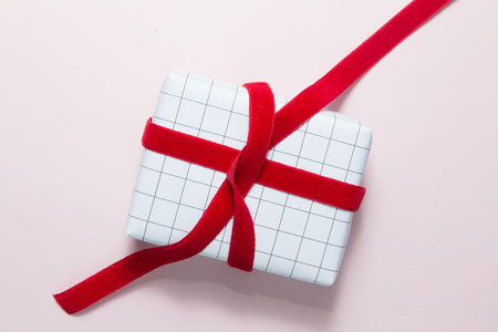 Top view of red ribbon with gift box on pink background. Stock Photo