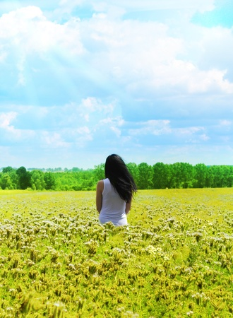 surrender:  Beautiful girl in a meadow with wild spring flowers Stock Photo