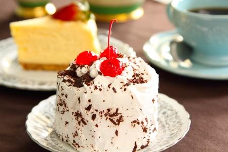 Cream cake with cherry on top photo