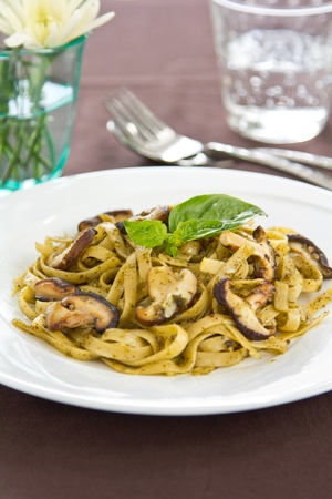 Fettuccine with mushroom in pesto sauce photo