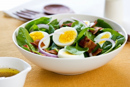 Bacon with boiled egg and spinach salad by salad dressing