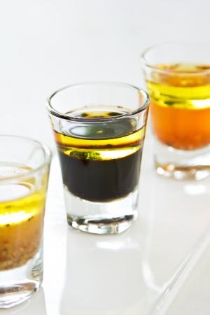 wholegrain mustard: Varieties of salad dressing in glasses shot