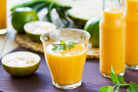 Pineapple with Orange and Mango smoothie in a glass and bottles photo