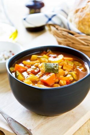Vegetables soup with chickpea by bread loaf photo
