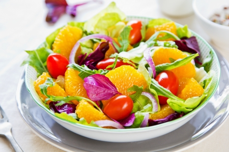 Orange with rocket and lettuce salad in a bowl Stock Photo