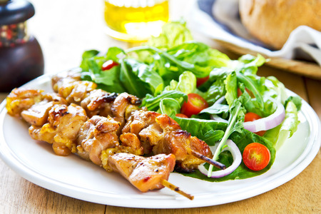 Grilled chicken skewer with rocket salad by bread