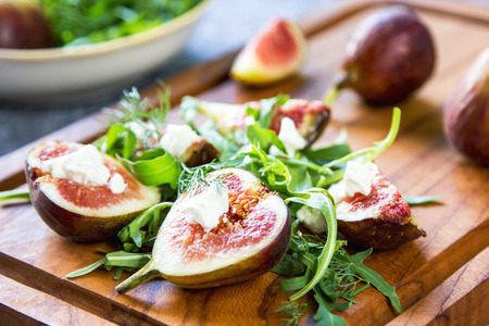purple fig: Fig with Goat cheese and Rocket salad on wooden chopping board Stock Photo