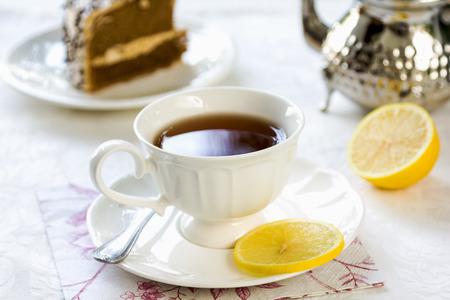 english tea: Black tea with lemon by a tea pot Stock Photo