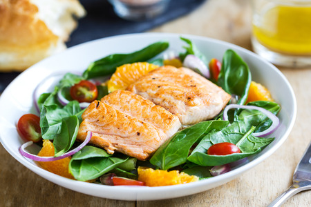 Salmon with orange and spinach salad by a loaf of bread photo