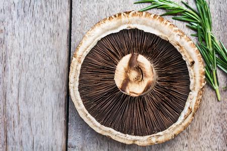 portobello: Fresh Portobello mushroom by rosemary  on wooden board