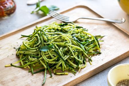 Zucchini spaghetti in Pesto sauce on wooden dish