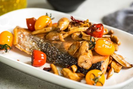 Salmón a la parrilla con champiñones salteados y tomates cherry con chile en vinagre balsámico Foto de archivo