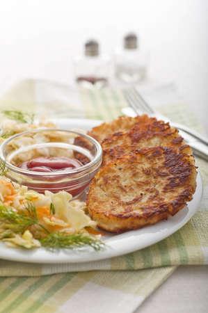 Potato patties - Rösti, with cabbage salad Stock Photo