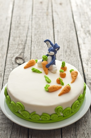 Homemade carrot cake with rabbit decoration on old wood table photo