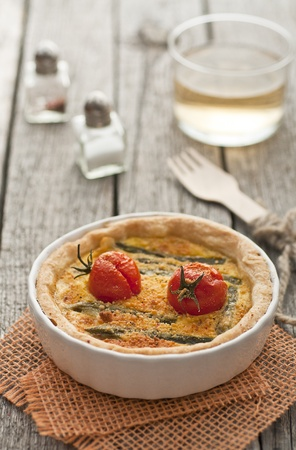 Quiche with asparagus and tomatoes with cup of wine