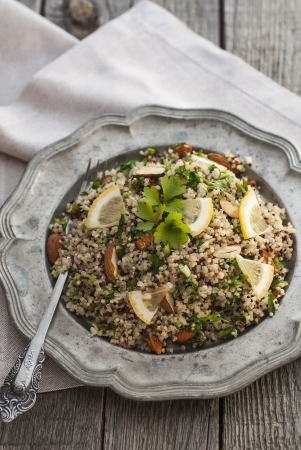 Quinoa salad with almonds and parsley served in old style plate photo