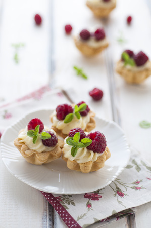 sweet pastry: Sweet tartalette with pastry cream, fresh raspberries and mint