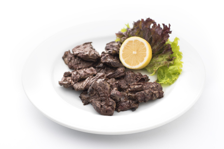 giblets: Duck hearts with lemon on fresh lettuce, isolated on white