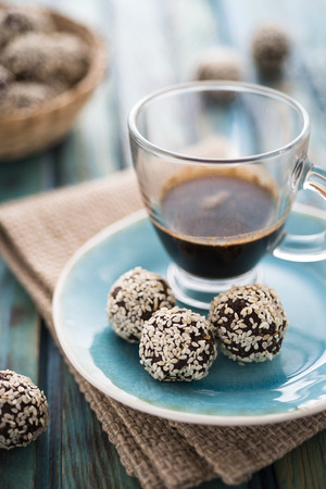 cafe bombon: Raw cocoa candies with sesame seeds and a cup of coffee