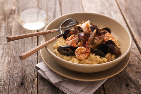 Saffron risotto with shrimps and mussels on vintage wood table