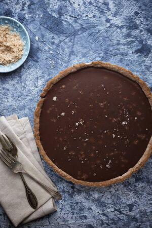 Chocolate tart with sea salt on blue table