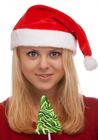 Young blond woman in santa hat with candy photo