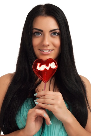 Portrait of a girl holding heart shape candy photo