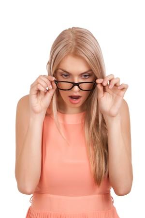 Verrast blonde vrouw naar beneden te kijken over glazen Stockfoto