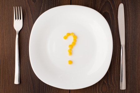 food questions: Question mark made of corn seeds on white plate