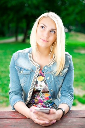 Young blond girl listening music in park photo