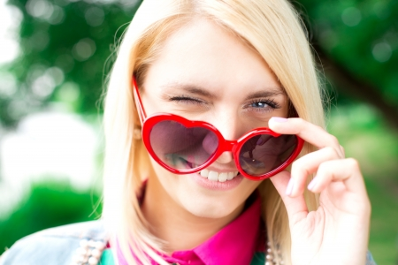 Portrait of beautiful woman with heart shape glasses in park photo