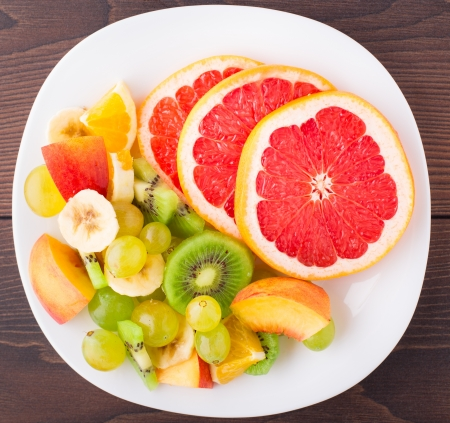 Assortment of sliced fruits on white plate photo