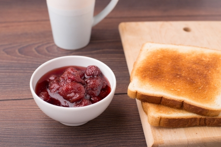 strawberry jam sandwich: Toast and strawberry jam on a wooden table Stock Photo