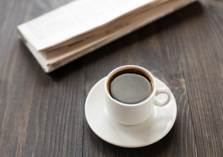 newspaper and cup of coffee on wooden table photo