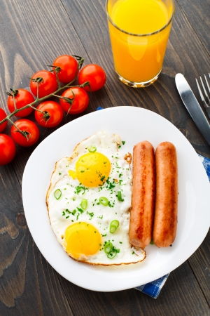 Fried eggs with sausages on a plate. Stock Photo